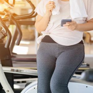 Person im Fitnessstudio schaut auf ihr Handy