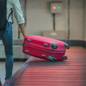 Frau nimmt Koffer von Gepäckband