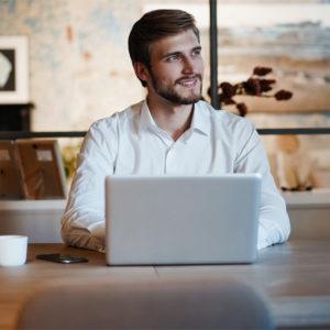 Mann sitzt vor Laptop an Küchentisch