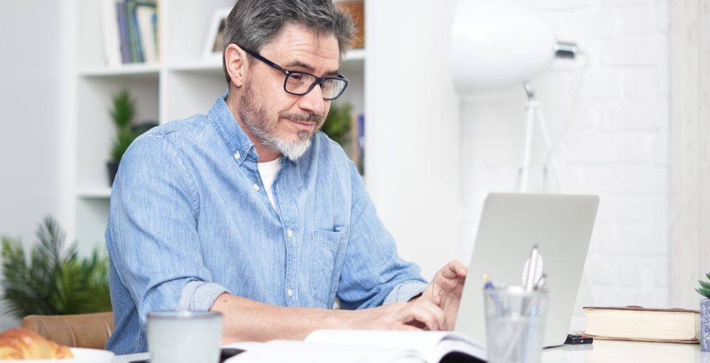 Mann sitzt im Homeoffice am Laptop