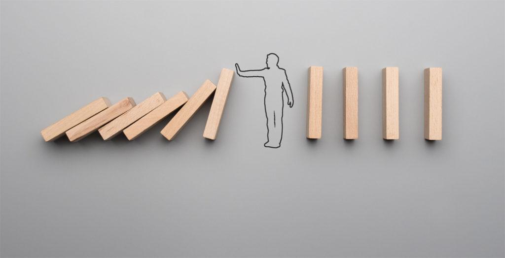 Mann zwischen Dominosteinen