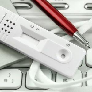 Corona-Test und Stift auf Tastatur