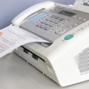 Hand zieht Dokument aus Faxgerät