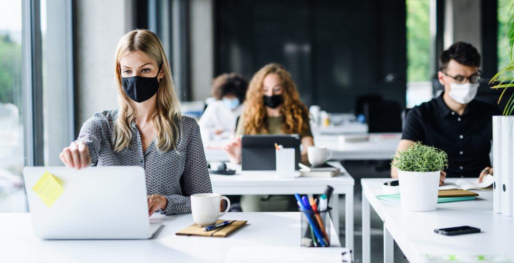 Auszubildende im Büro tragen Mundschutz
