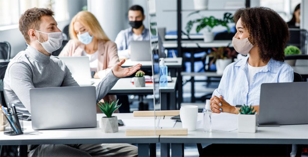 Büro-Mitarbeiter mit Mundschutz und Plexiglasscheibe