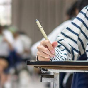 Hand mit Stift in Schulsituation