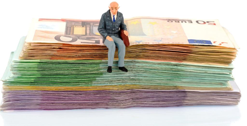 Älterer Mann sitzt auf einem Bündel Geldscheine
