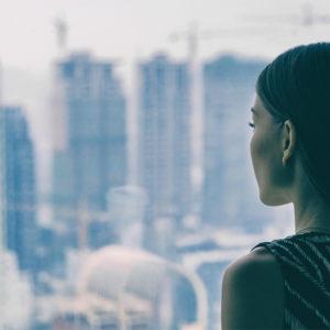 Junge Frau blickt auf Wolkenkratzer in der Ferne
