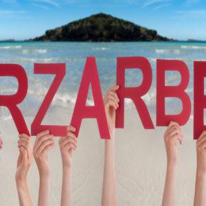 """Hände halten Buchstaben """"Kurzarbeit"""" vor Urlaubskulisse hoch"""