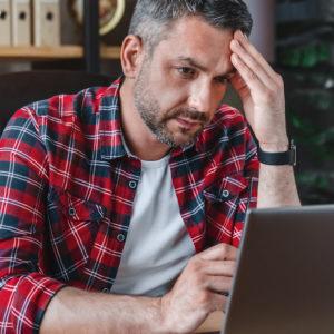Mann gestresst am Laptop