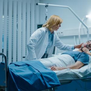 Patient im Krankenhaus mit zwei Pflegerinnen.