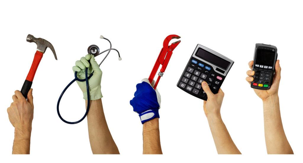 Hände halten verschiedene berufliche Werkzeuge in die Luft