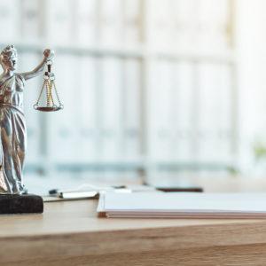 Justitia Statue auf einem Bürotisch