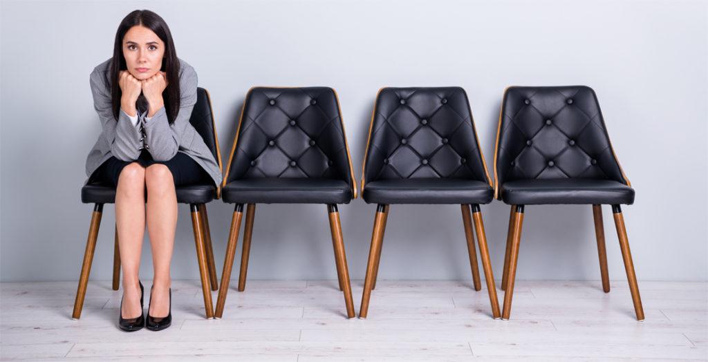 Bewerberin sitzt genervt auf dem linken einer Reihe von Stühlen