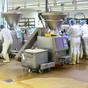 Menschen stellen Wurst in einer Fleischfabrik her
