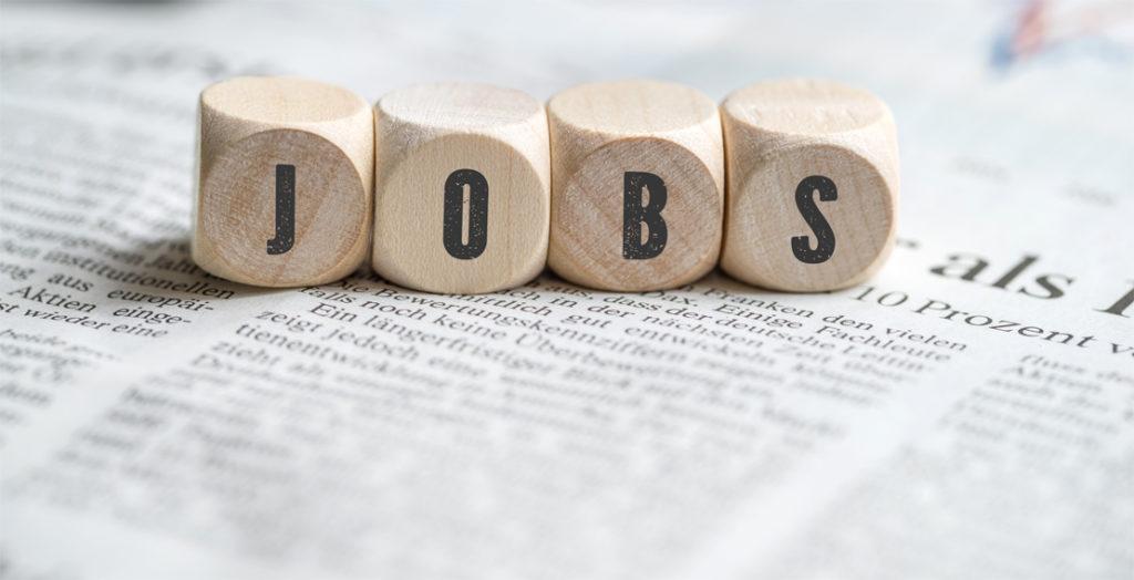 Holzwürfel mit Aufschrift Jobs auf Tageszeitung