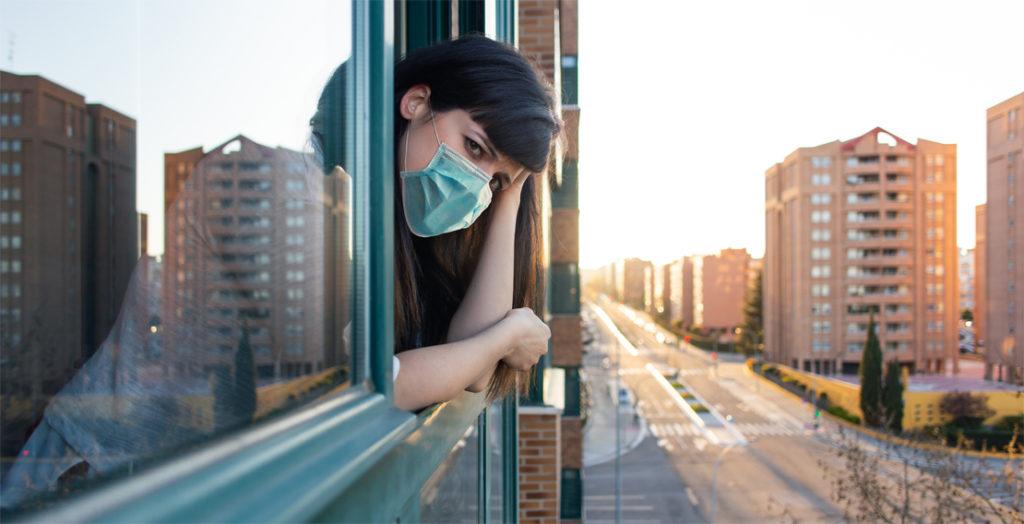 Frau mit Mundschutz schaut betrübt aus dem Fenster