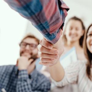 Handschlag für junge Mitarbeiterin mit ihrem Team