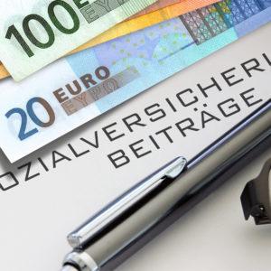 Geldscheine, Stift, Brille und Schriftzug Sozialversicherungsbeiträge