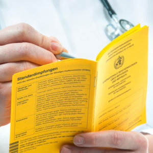 Arzt schreibt in Impfausweis
