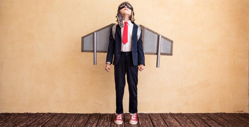 Junge im Anzug mit Raketenantrieb auf dem Rücken