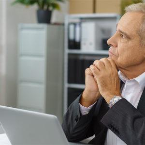 Älterer Arbeitnehmer vor Laptop schaut nachdenklich in die Ferne