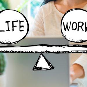 Frau am heimischen Laptop, davor gezeichnete Work-Life-Waage