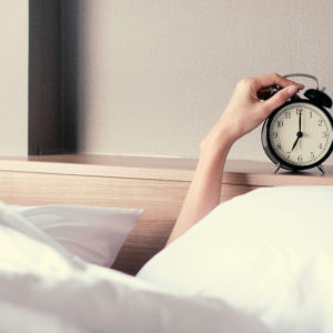 Frau im Bett stellt den Weckeralarm aus