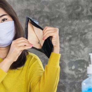 Frau mit Mundschutz zeigt leeres Portemonnaie