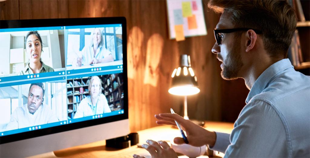 Geschäftsmann führt Videokonferenz vom heimischen Schreibtisch